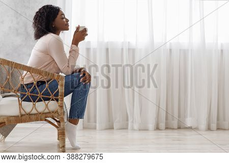 Relaxing Morning. Side View Portrait Of Calm Black Female Sitting In Wicker Chair Enjoying Coffee, R