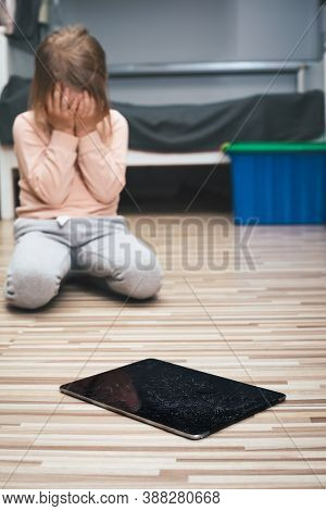 Upset little girl crying afraid of being punished for accidentally broke a tablet computer. Focus on cracked touch screen of a tablet in foregroung