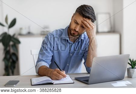 Serious Millennial Businessman Taking Notes And Working On Laptop Computer In Modern Office, Busy En