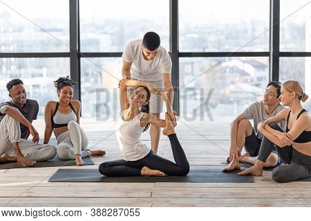Professional Yoga Instructor Helping To Group Member In Difficult Asana, Coach Correcting Posture Of