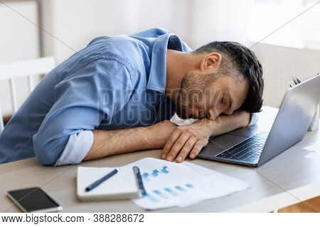 Sleep At Work. Exhausted Overworked Man Employee Napping At Workplace In Modern Office, Tired After