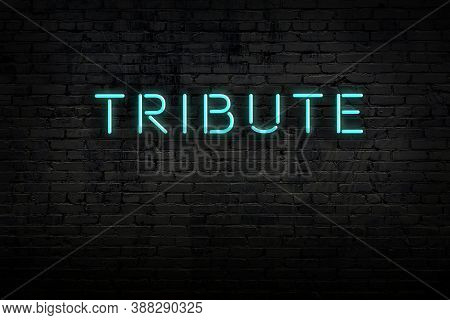 Neon Sign On Brick Wall At Night. Inscription Tribute