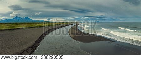 Aerial view of estuary on Khalaktyrsky beach with black sand and volcano on Kamchatka peninsula, Russia, Pacific ocean