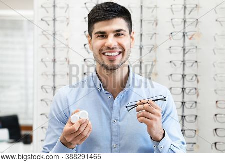 Ophthalmology Concept. Portrait Of Smiling Young Man With Myopia Showing To Camera Eyeglasses And Co