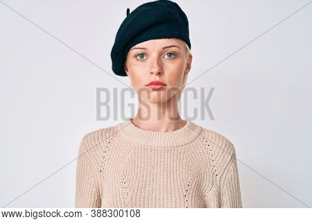 Young blonde woman wearing french look with beret with serious expression on face. simple and natural looking at the camera.