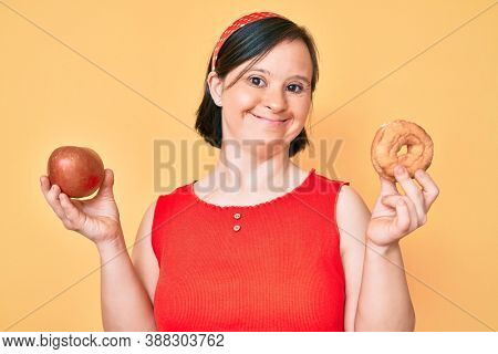 Brunette woman with down syndrome holding red apple and donut sitting smiling with a happy and cool smile on face. showing teeth.