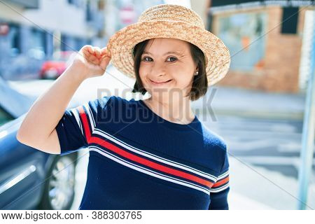 Beautiful brunette woman with down syndrome wearing a summer hat at the town on a sunny day