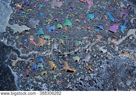 Colorful Gas Stain On Wet Asphalt. Oil Stain Caused By A Leak Under A Car Or Truck.