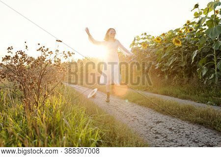 Cheerful young female in white dress having fun while moving down footpath between sunflower fields and enjoying sunny day