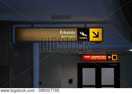 Arrivals hall sign at an airport with dim light and no people. The first line in Hungarian language saying arrivals, sign in the back says Offices - staff only in Hungarian and English