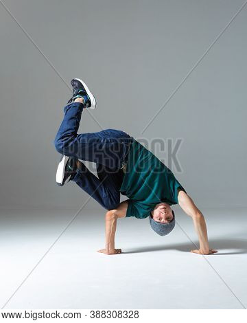 Cool Guy Breakdancer In Hat Stands On Hands Dancing Isolated On Gray Background. Dance School Poster