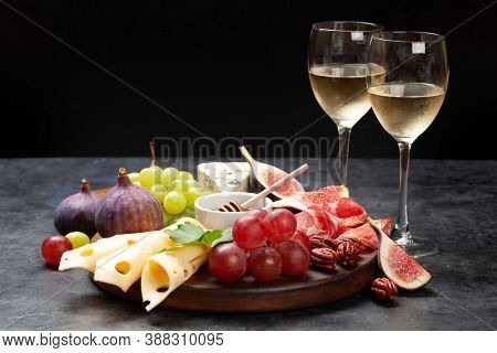 Antipasto plate with prosciutto, cheese, figs and grapes. Appetizer board and white wine. With copy space