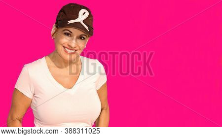 Beautiful Woman Wearing A Hat With A Pink Ribbon Isolated On A Pink Background In Support Of Breast