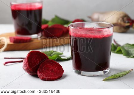 Two Glass Of Fresh Beetroot Juice And Chopped Beet On Wooden Board On Gray Table. Close Up. Horizont