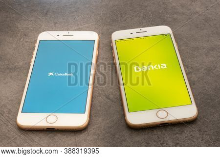 Barcelona, Spain; October 4 2020; Smartphones with spanish banks Applications on the screen. Caixabank and Bankia merger concept