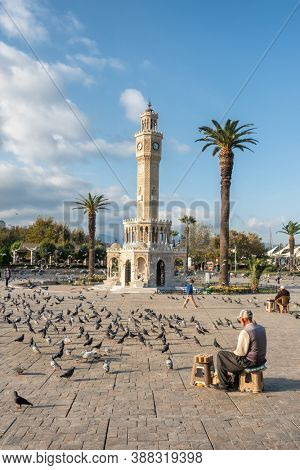 Izmir, Turkey - November 6, 2019: Unidentified turkish senior man selling food for pigeons near the Clock Tower of Izmir at Konak Square