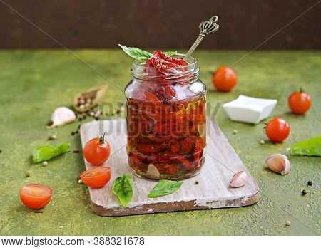 Homemade Sun Dried Tomatoes In A Glass Jar On An Olive Green Concrete Background. Canning, Preserves