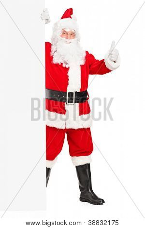 Full length portrait of a Santa claus holding a blank billboard and giving a thumb up