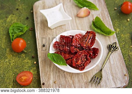 Homemade Sun-dried Tomatoes In A White Bowl On A Wooden Board On An Olive Green Concrete Background.