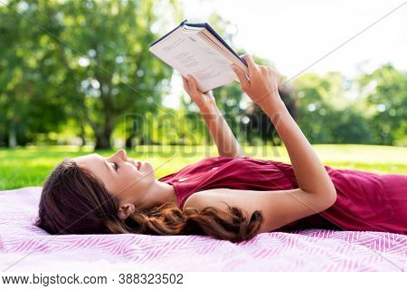 leisure and people concept - happy smiling woman reading book lying on picnic blanket at summer park