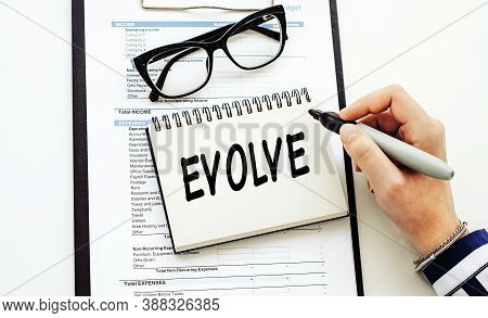 Evolve. Text On White Notepad On Documents