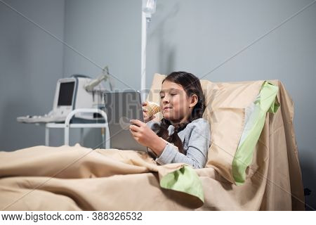 Teenage Female Patient Relaxing In Hospital Bed With Digital Tablet.
