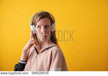 Young Woman Wearing White Headphones Making A Goofy Face. Over Bright Yellow Background.