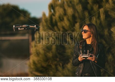 Young Modern Smiling Woman Pilot In Dark Stylish Clothes Operating The Drone By Remote Control. Flyi