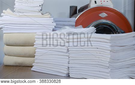 Stack Of Folded Clean Cloths In An Industrial Laundry.  Cleaning Service For Institutions, Hotels, H