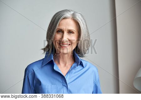 Smiling Sophisticated Mature Grey-haired Woman Standing On Grey Wall Background At Home. Happy Elega