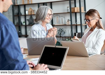 Smiling Mature Old Female Mentor Coach Supervisor Training Young Interns At Group Office Meeting Pro