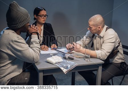 An Experienced Investigator During The Interrogation Shows The Alleged Criminal And His Lawyer Evide