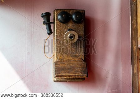 Old Fashioned Telephone Earphone From The 1900s, On A Wall. Pink Background