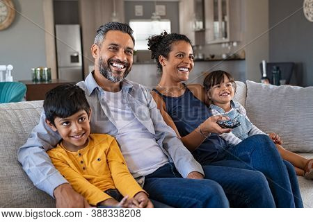 Happy indian man and african woman relaxing with daughter and son watching television at home together. Cheerful ethnic family relaxing on sofa at home watching movie with children.