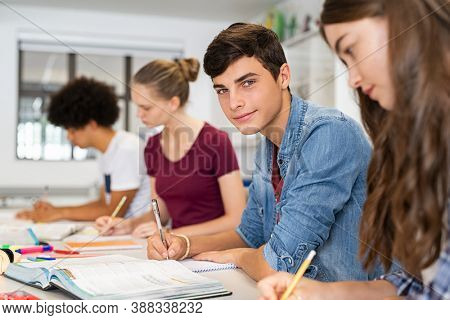 Portrait of happy college young man studying with classmates. Group of friends studying together while sitting in university classroom. High school guy looking at camera while sitting in a row at desk