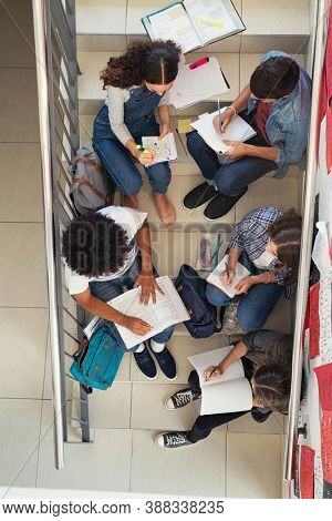 High angle view of high school students group sitting on staircase and studying together for next exam. Top view of young group of classmates doing homework sitting on college staircase.