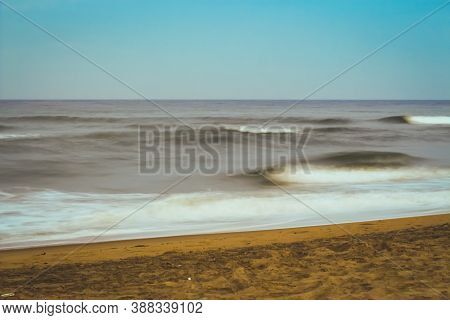 Beautiful Beach View Over The Sunset Colorful Sky. Moving Elements And Wave Photography From The Bea