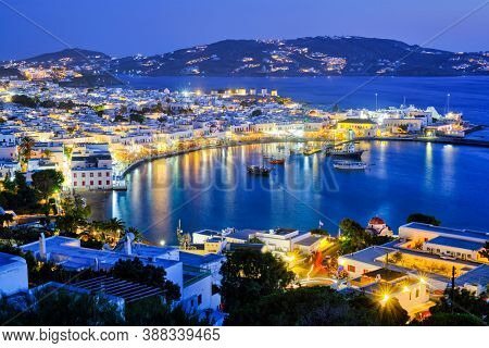 View of Mykonos Chora town Greek tourist holiday vacation destination with famous windmills, and port with boats and yachts illuminated in the evening blue hour . Mykonos, Cyclades islands, Greece