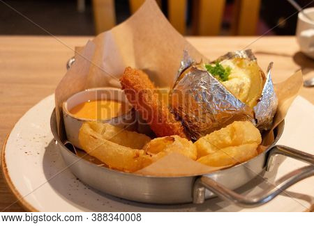 Golden Brown American Appetizers In Bowl On White Plate On Wooden Table