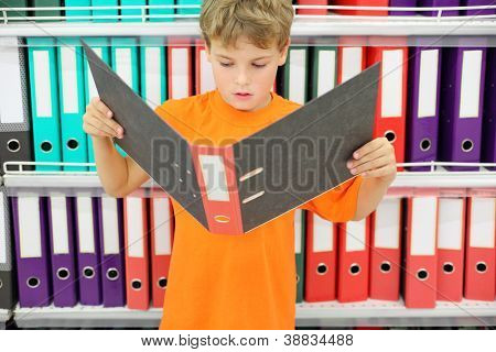 Boy in orange shirt looks big folder and stands near to shelves with folders.