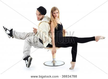 Rapper and ballerina sit on yellow chair and look at camera isolated on white background.