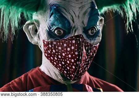 closeup of a disturbing evil clown, with green hair, wearing a dirty red costume and a dirty bow tie, wears a red face mask patterned with white dots, in front of the circus tent