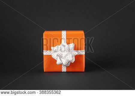 Wrapped Handmade Present In Orange Paper With Bow On Black Background. Present Box With Copy Space.