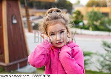 A Little Girl In A Pink Hoodie With A Sad And Tearful Face Is Holding Her Ear. Ear Pain, Otitis Medi