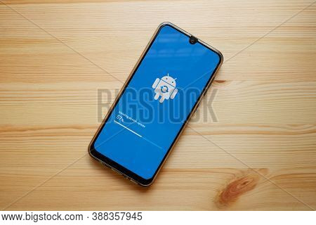 Bangkok, Thailand- October 1, 2020 Smartphone Whose Screen Is Updating To Android System On Wooden B