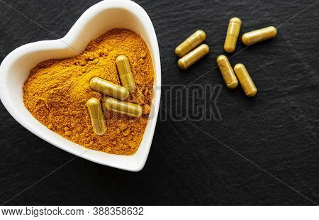 Turmeric Powder And Turmeric Pills On A Black Concrete Background
