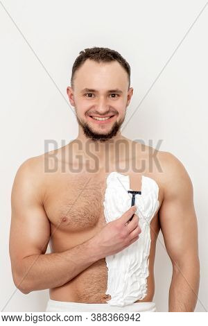 Young Caucasian Man With Beard Holds Razor Shaves His Chest With White Shaving Foam On White Backgro