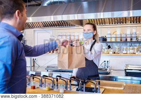 Young Waitress Waring Protective Face Mask And Apron Serving Takeaway Food To Customer At Counter In