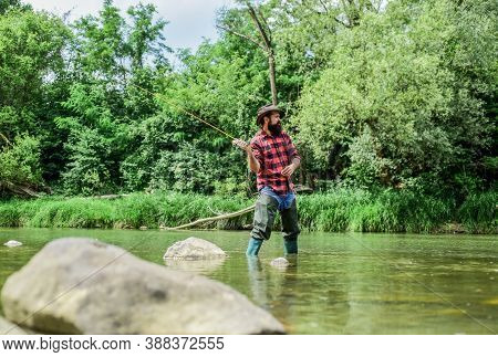 Experience The Legend. Experienced Fisher In Water. Man Catching Fish. Mature Man Fly Fishing. Fishe