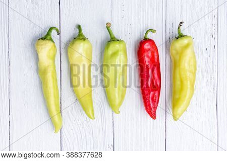 Single Red Chili Pepper Among Green Peppers On White Wooden Table. Concept Of Difference